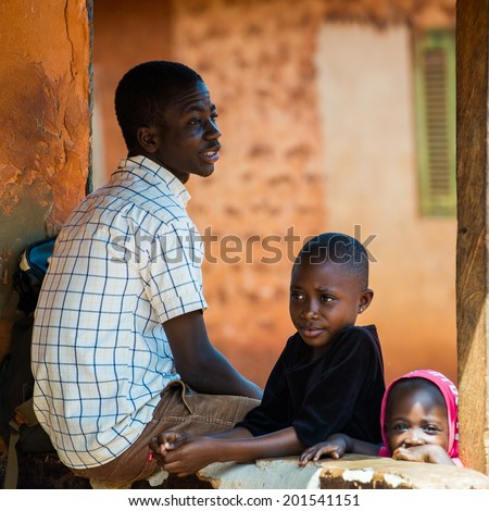 ACCRA, GHANA - MARCH 5, 2012: Unidentified Ghanaian man and his children near the housein the street in Ghana. People of Ghana suffer of poverty due to the unstable economic situation
