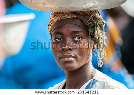 ACCRA, GHANA - MARCH 4, 2012: Unidentified Ghanaian woman trasports a pelvis over her head in Ghana. People of Ghana suffer of poverty due to the unstable economic situation - stock photo