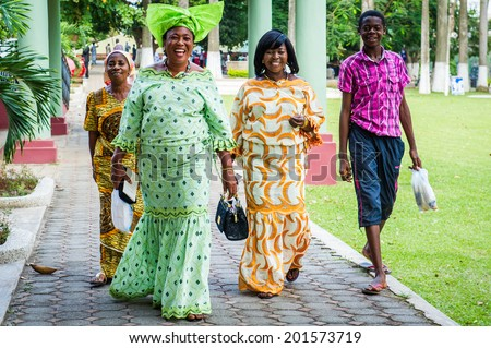 ACCRA, GHANA - MARCH 3, 2012: Unidentified Ghanaian women walk on the grass in bright dresses in the street in Ghana. People of Ghana suffer of poverty due to the unstable economic situation - stock photo