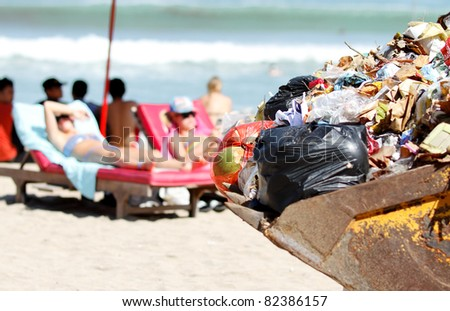 accumulation people trash on the beach loaded on a backhoe - stock photo