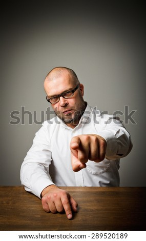 Accusation. Man at a long wooden table is indicating something. - stock photo
