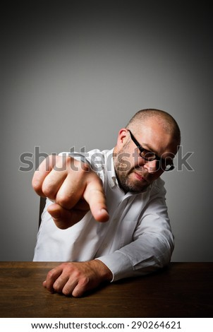 Accusation. Man at a long wooden table is indicating