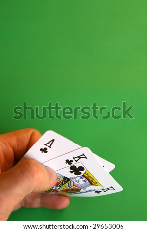 ace and king clubs in the hand on green background ... - stock photo