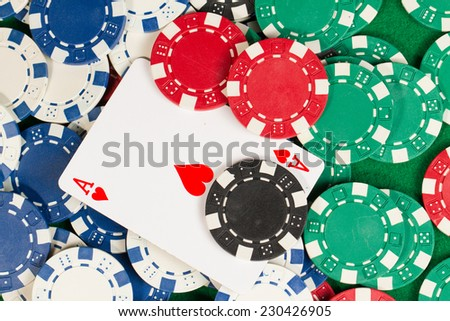 Ace card in the middle of green, red, blue, white and black Playing Poker Chips in a green background