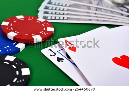 Ace, jack and poker chips on table - stock photo