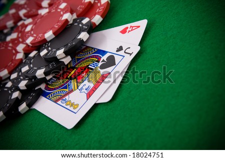 Ace of hearts and black jack with black and red poker chips in the background. - stock photo