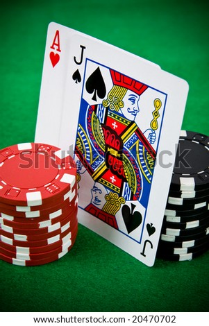 Ace of hearts and black jack with black and red poker chips on green poker table. - stock photo