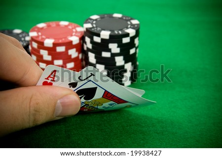 Ace of hearts and black jack with red poker chips in the background. - stock photo