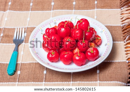 acerola in plate and fork on hand made cotton napery