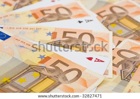 aces between lots of 50 euro bills. focus on the heart of the ace in the forground.