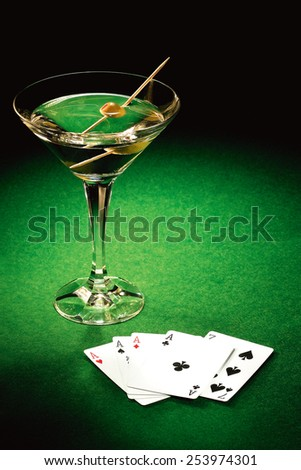Aces winning card hand laid on green felt poker table with deck of cards and martini pimento olive on cocktail stick - stock photo