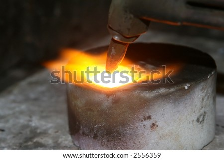acetylene torch smelting hot precious metals, macro close up with copy space - stock photo