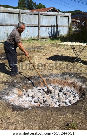 ACHAO, CHILE - FEBRUARY 6, 2016: Unidentified man preparing the hole with hot stones for the traditional Chilotan dish Curanto al hoyo at the Muestras Gastronomicas 2016 Gastronomy Show in Achao