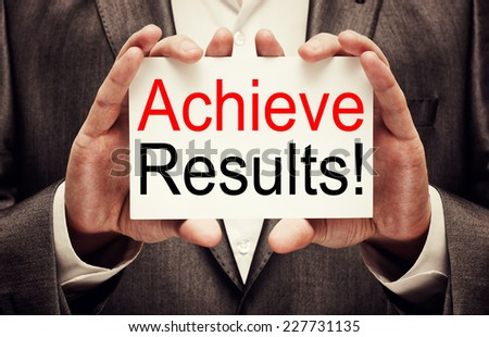 Achieve results ! Businessman holding a card with a motivational message written on it - stock photo