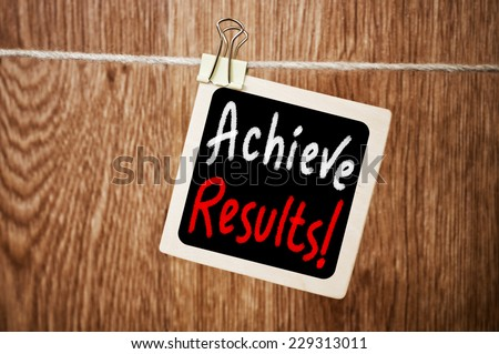 Achieve results ! written on a chalkboard with a wood wall in a background - stock photo