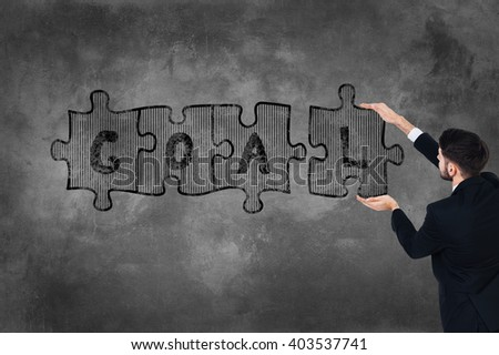 Achieve your goal! Rear view of young man in full suit touching concrete wall with illustrated puzzle on it  - stock photo