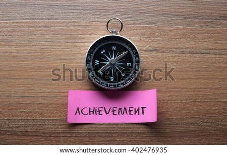 Achievement : Motivation advice handwriting on label with compass - stock photo