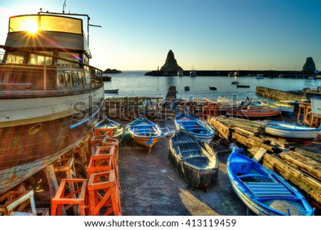 Acitrezza harbor with old boat and lachea island in Sicily, Italy - stock photo