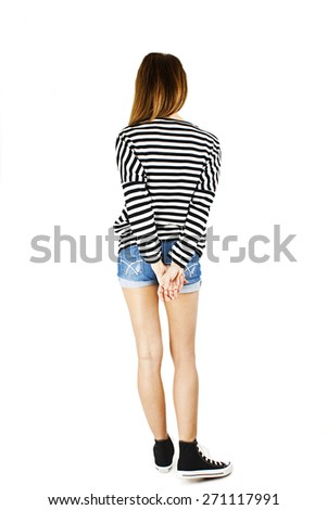 ack view of young woman in denim shorts and striped sweatshirt looking at wall. The rear view. Isolated over white background. - stock photo