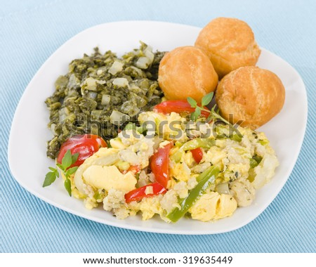 Ackee & Saltfish - Traditional Jamaican dish made of salt cod and ackee fruit. Served with callaloo and johnny cakes. - stock photo