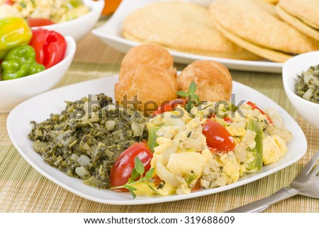 Ackee & Saltfish - Traditional Jamaican dish made of salt cod and ackee fruit. Served with callaloo and johnny cakes. Patties on background.