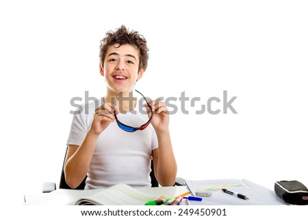 Acne Caucasian teenager holding black plastic 3D Cinema eyeglasses with both hands while doing  homework - stock photo