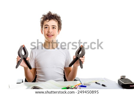 Acne Caucasian teenager smiles holding a couple of black plastic tongs while doing  homework - stock photo