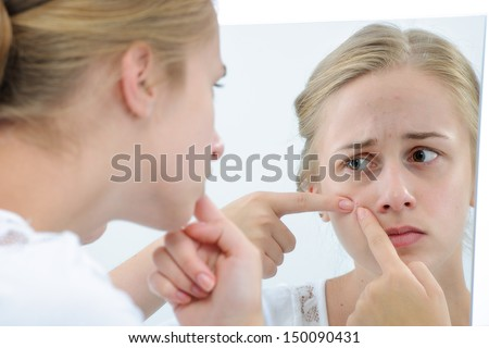 Acne facial care teenager woman squeezing pimple - stock photo