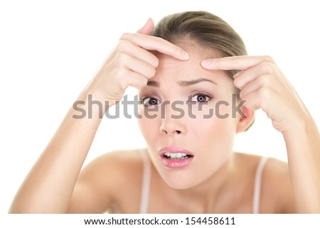 Acne spot pimple spot skincare beauty care girl pressing on skin problem face. Woman with skin blemish looking at mirror isolated, white background. Beautiful young Asian Caucasian female model. - stock photo