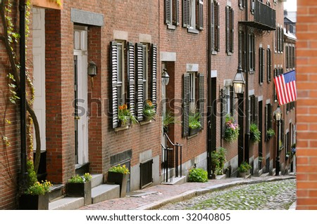 Acorn Street in Beacon Hill, Boston. Brick apartment facades, flower pots framing house entrance, window box, lamps and cobblestone way. Tourist attraction, historic landmark, nice place to walk by. - stock photo