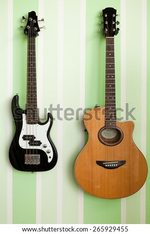acoustic and electro guitar on the wall - stock photo