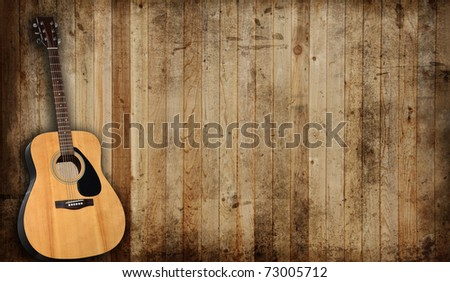 Acoustic guitar against an old barn background. - stock photo