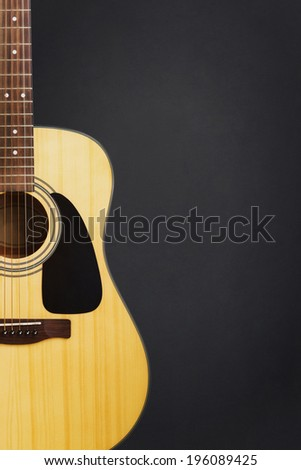 Acoustic guitar against bank chalkboard background - stock photo