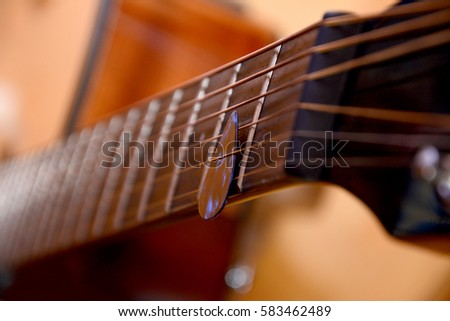 Acoustic guitar and pick, close up view.