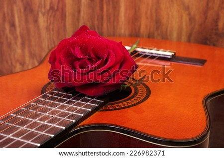 Acoustic Guitar And Red Rose Wooden Background
