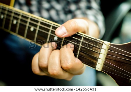 Acoustic guitar being played, Fingers holding a chord.