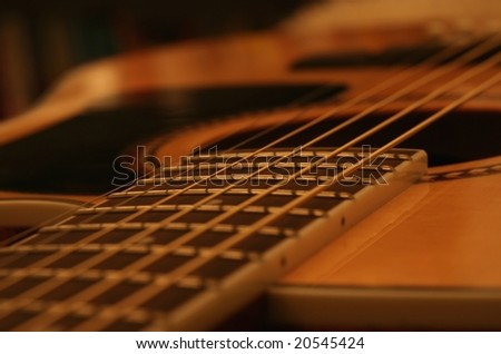 Acoustic guitar body and fret board close up.