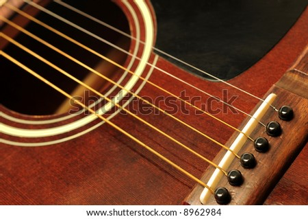 Acoustic guitar bridge and strings close up - stock photo