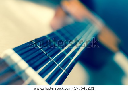 Acoustic Guitar focus to fret on fingerboard, shallow depth of field, old film processed - stock photo