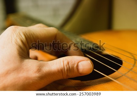 Acoustic guitar guitarist playing. Musical instrument with performer hands. Artist art song - stock photo