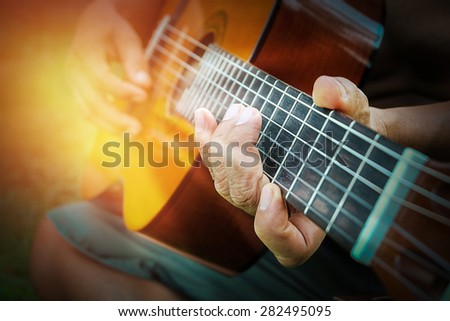 Acoustic guitar in male hands, close-up