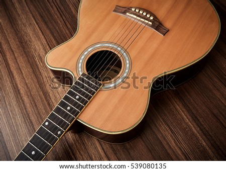 Acoustic guitar laid on wooden floor background.