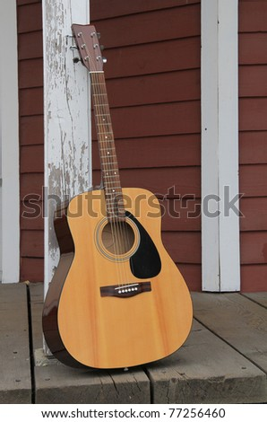 Acoustic guitar leaning against a barn post. - stock photo