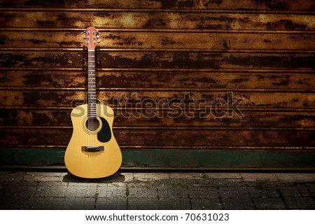 Acoustic guitar leaning  on rusty  gates - stock photo