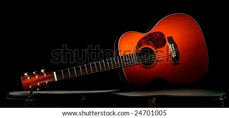 acoustic guitar lying on the case, dramatic lighting. - stock photo