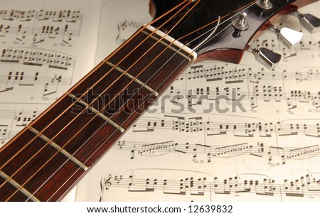 Acoustic guitar neck and tuning pegs with sheet music background