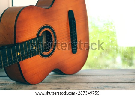 Acoustic guitar next the window with rain drops - stock photo