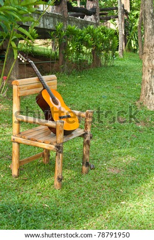 Acoustic Guitar on old rocking chair on grass - stock photo