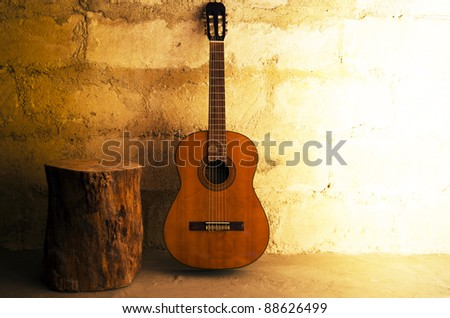 Acoustic guitar on old wall and stump - stock photo