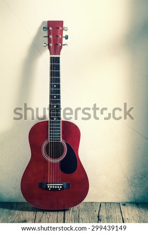 acoustic guitar on old wood with grunge wall ( cross process color tone ) - stock photo